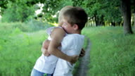 Two brother huging each other outdoor, smiling and laughing, 1080p video