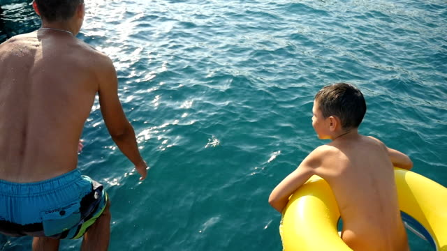Two brothers, big and small, jump feet first in sea waters in summer in slo-mo video