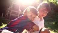 Two brothers together posing for photo in the sunlight. Kid brothers hugging each other video