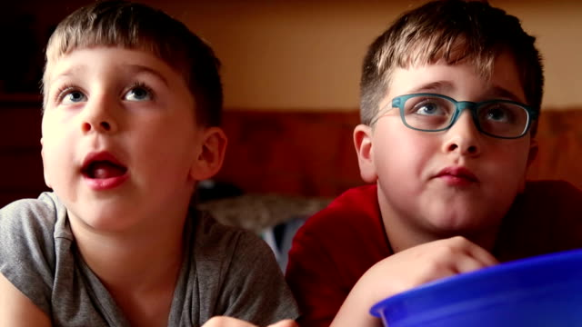 two brothers watching tv and nibbled snacks video