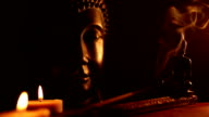 two Buddha statue with candles and incense video