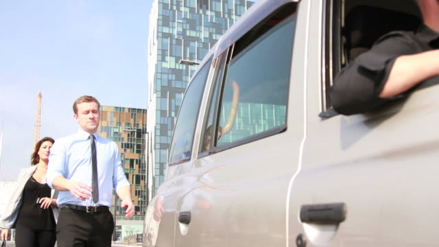 Two Business executives getting into back of taxi video