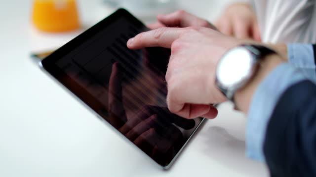 Two business people using digital tablet on coffee break video