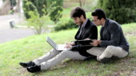 Two business people with tablet and laptop talk about a project on a park video