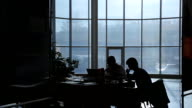 Two business persons work in dark office in evening video
