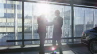 Two businessman have a conversation and reach an agreement with a handshake at a garage parking lot. video