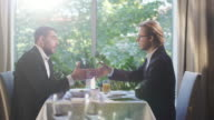 Two businessman in suits have a conversation and reach an agreement with a handshake at a restaurant. video