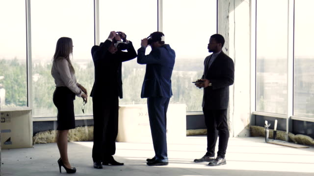 Two businessmen in oculus rift near two colleagues in building video