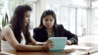 Two Businesswomen Discussing Project on Tablet video