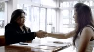 Two Businesswomen Handshaking and Signing Contract video