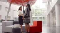 Two Businesswomen Shaking Hands In Lobby Of Modern Office video