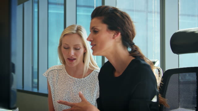 Two Businesswomen Working At Desks Have Discussion Together video