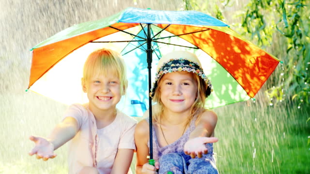 Two carefree girl sit under an umbrella, hiding from the warm summer rain. The concept - a happy childhood video