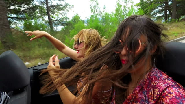 Two carefree girls partying while riding in cabriolet video