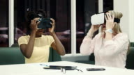 Two caucasian and afro-american women using virtual reality glasses video