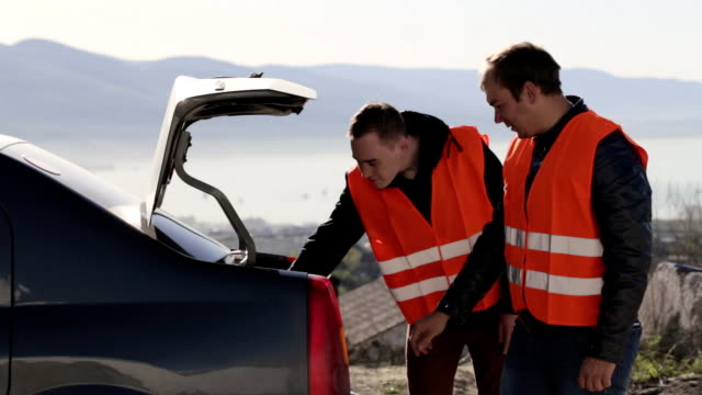 Two caucasian men removing equipment from the trunk video