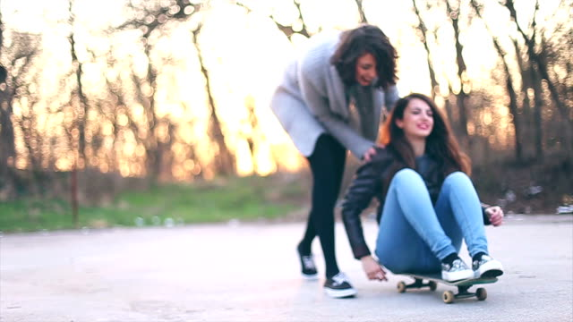 Two cheerful friends with skateboard having fun video