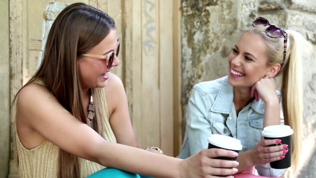 Two Cheerful girl friends drinking coffee video