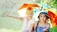 Two cheerful girlfriends five years hiding from the rain under an umbrella rainbow colors. Happy childhood, friendship video