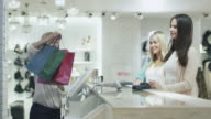 Two cheerful young girls are buying clothes at a cash desk in a department store. video