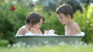 Two children, boy brothers, having a bath outdoors, making soap bubbles, summertime video