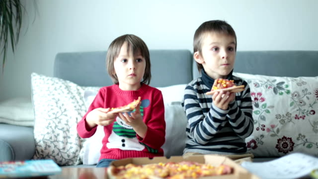 Two children, boys, eating pizza at home while watching TV video