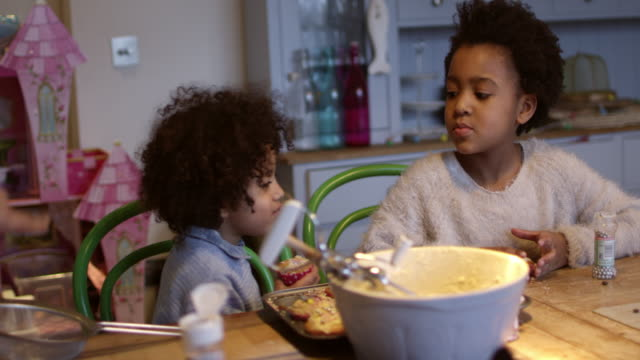Two Children Eating Homemade Cupcakes At Table Shot On R3D video