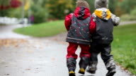 Two children, fighting over toy in the park on a rainy day, autumn time video