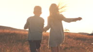 Two children holding hands, running together outdoors video