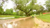 Two Children Running In Puddles In Park video