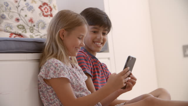 Two Children Sitting On Floor And Playing With Smartphone video