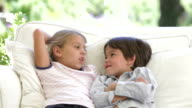 Two Children Talking Together Sitting On Sofa video