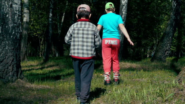 Two children walk through the green woods (slow motion) video