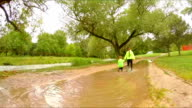 Two Children Walking In Puddles In Park video