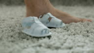 Two children's sandals close to a man's foot. video