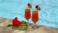 Two cocktails by pool with tropical flower. video