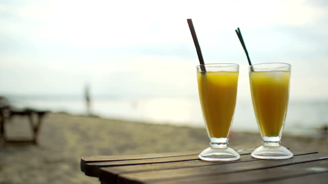 Two cocktails on wooden table by the sea video