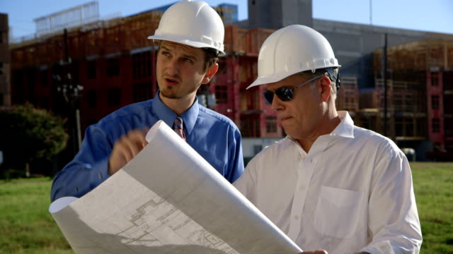 two construction engineers going over building plans video