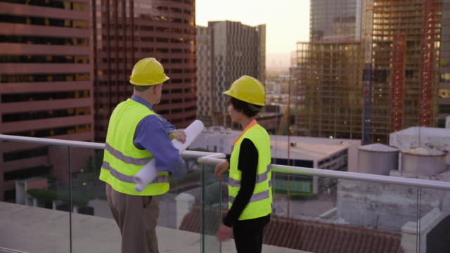 Two construction supervisors look at plans on rooftop video