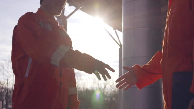 Two construction workers in orange uniform and hardhats shaking hands at the bulding object video