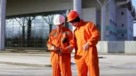 Two construction workers in orange uniform and helmets looking over plans together. Building at the background video
