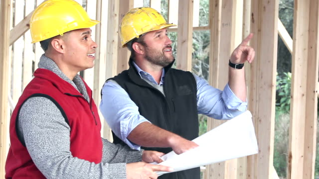 Two construction workers or contractors at job site video