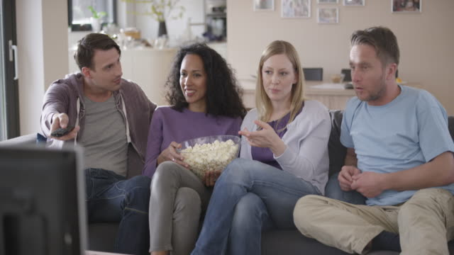 Two couples watching TV, talking and eating popcorn video