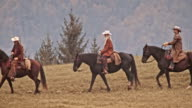 TS Two cowboys and a cowgirl riding horse on mountain video
