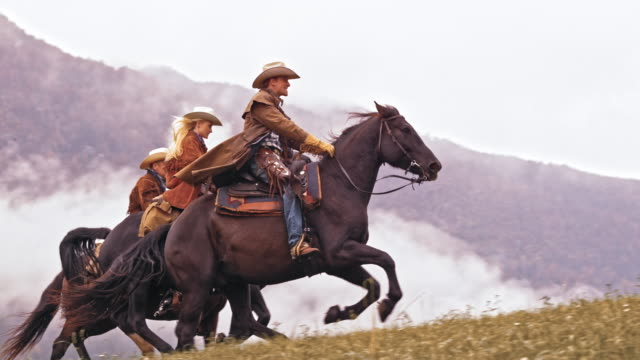 SLO MO DS Two cowboys and cowgirl riding galloping horses video