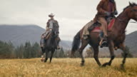 SLO MO Two cowboys riding galloping horses in mountains video