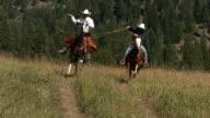 Two cowboys riding horseback swinging lassos, slow moiton video
