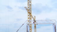Two crane working together at building site with sky background video