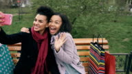Two cute african american woman taking selfie on smartphone with shopping bags and smiling. Girlfriends sitting on street bench have fun after visiting mall sales video