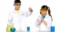Two cute chemist children making interesting and successful experiments with blue foam isolated on white background, slow motion video